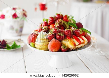 Beautifully decorated catering serving of fresh fruits on white wooden table. Birthday party, corporate event, wedding celebration composition