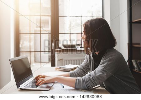 Young female blogger working at home. Beautiful woman sitting in working room and typing on laptop with blank screen