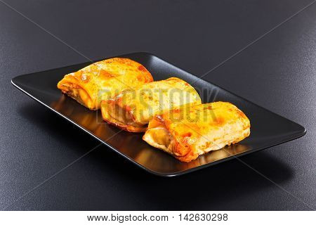 rolled pancakes or crepes stuffed with minced meat and vegetables on black dish on dark background view from above close-up