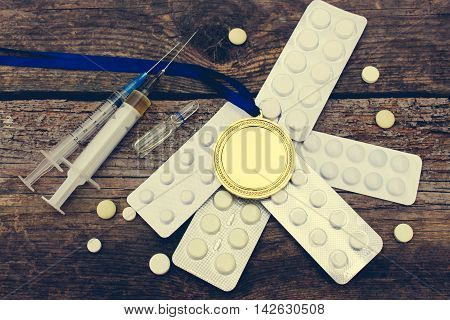 Sports medal and medicines on a wooden background. Toned image.