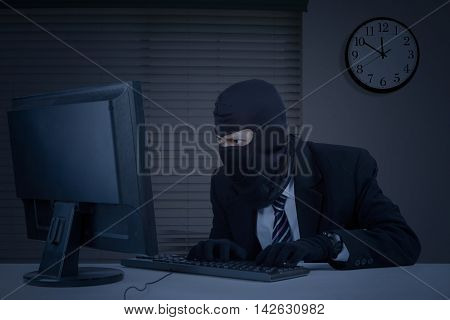 Male thief wearing mask and steal information on the computer in the office at night