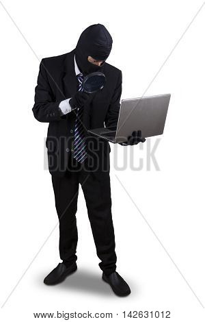 Male thief using magnifying glass to find information on the laptop isolated on white background