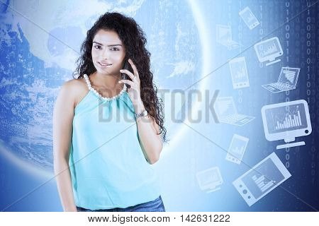 Global business communication concept. Young woman talking on the cellular phone with background of earth and financial graph on computer