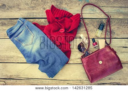Women's autumn clothing and accessories: red sweater, jeans, handbag, beads, sunglasses and cosmetics on wooden background. Toned image.