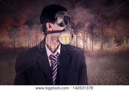 Male worker wearing a gas mask and formal suit with forest fire background