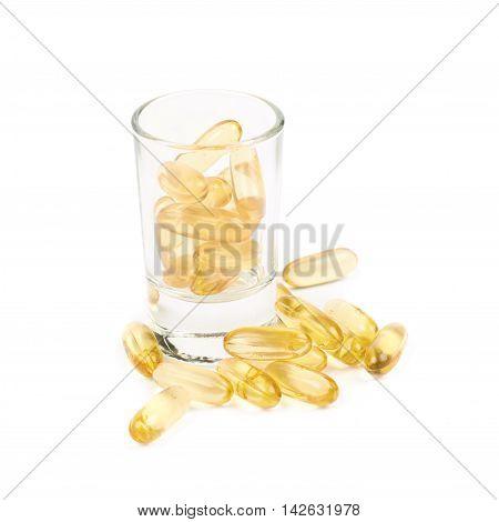Shot glass full of softgel pills isolated over the white background