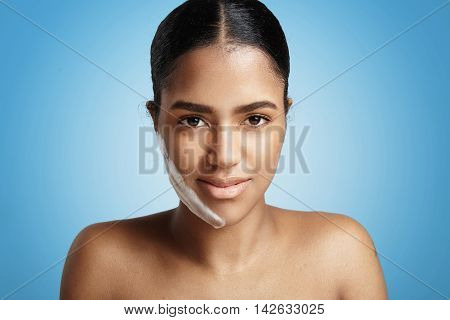 Closeup Portrait Of Woman With A Fase Cleansing Foam On The Cheek On Blue