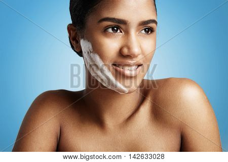 Woman With A Fase Cleansing Foam On The Cheek On Blue