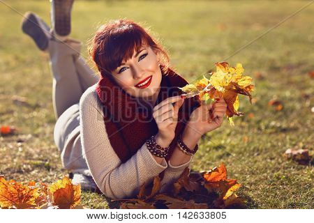 Beautiful young woman lying on ground and holding fall yellow maple leaves in hands. Outside shot. Autumn season.