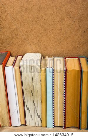 Colorful composition with vintage old hardback books, diary on wooden deck table and yellow background. Books stacking. Back to school. Copy Space. Education background