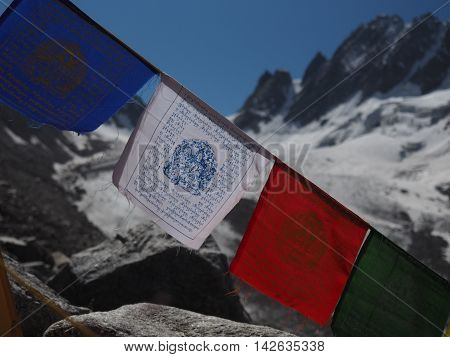 colorfull tibetan buddist nepal flags on the background of snowy mountains close-up
