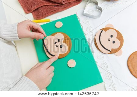 Children hands making  funny christmas gingerbread monkey head shape cookies