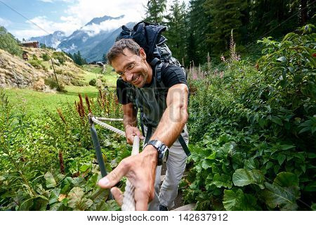 hiker in the Apls mountains. Trek near Matterhorn mount. a man with a happy face on a rope climbs