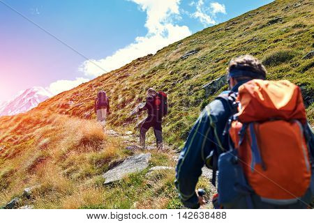 hikers with backpacks on the trail in the Apls mountains. Trek near Matterhorn mount