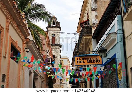 HAVANA, CUBA - March, 2013:  Calle Empedrado street. View on famous restaurant-bar La Bodeguita del medio, festive decorated with garlands, cathedral tower in background.  favourite pub of Hemingway.