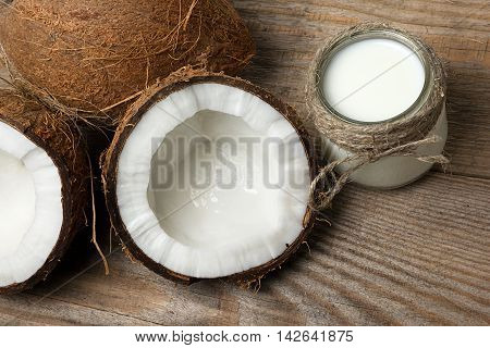 Exotic coconuts, coconut butter and milk on wooden background. Organic healthy food concept. Beauty and SPA concept.