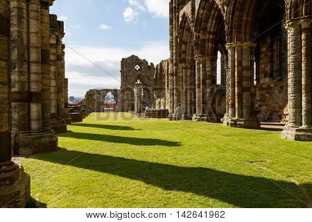 WHITBY, ENGLAND - AUGUST 12: Tourists visiting the ruins of Whitby Abbey. In Whitby, North Yorkshire, England. On 12th August 2016
