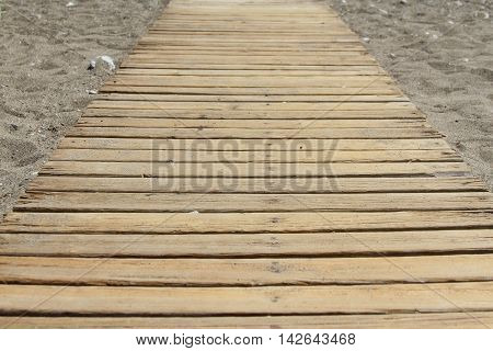 Wooden pier is passes through the rocky beach