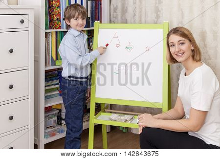 Cute elementary school student at the blackboard lesson answers. Beautiful young female teacher sitting next to him. She looks at the camera and smiling