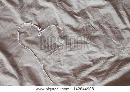 Heart shape earphone on gray blanket in the bed