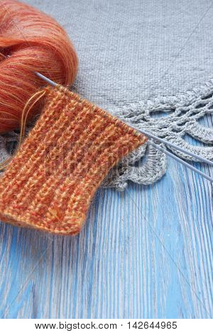 Knitting orange mohair wool on linen rustic background. The beginning on knit cloth