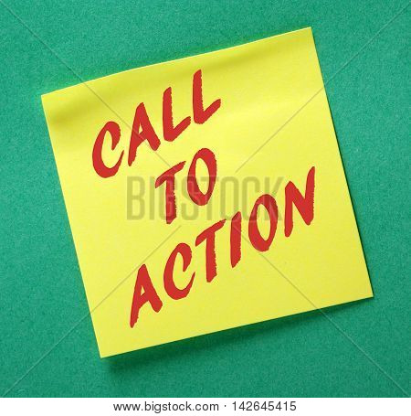The phrase Call to Action in red text on a yellow sticky note posted on a green notice board as a reminder