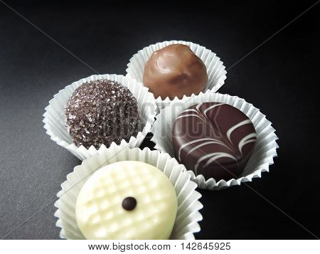 Various chocolate truffles in paper, isolated on black.