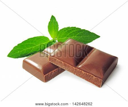 Chocolate pieces and mint leaves, milk chocolate isolated on white background.