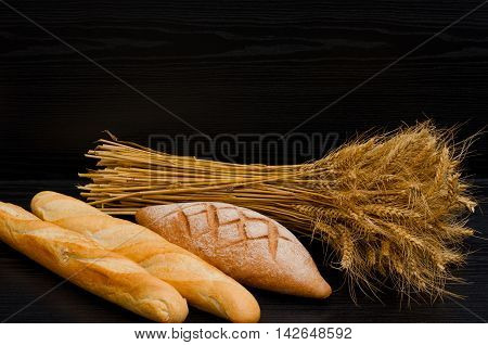 Two white loaf rye bread and a sheaf on a black background