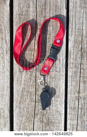 whistle on a red ribbon lying on wooden boards
