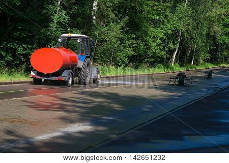 The machine washes and cools the road in the park