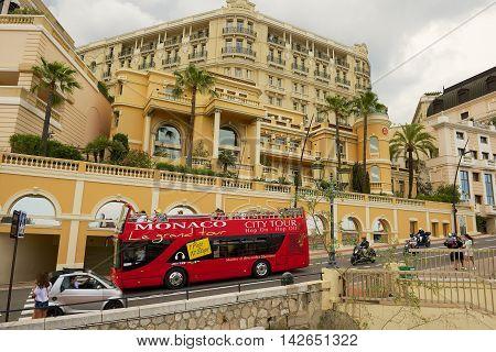 MONACO, MONACO - JUNE 17, 2015: Unidentified people enjoy sightseeing tour on the red Monaco city tour bus in Monaco.