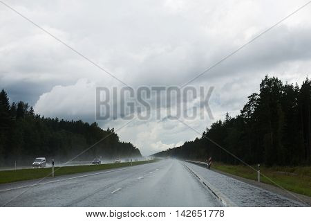 Ominous blue clouds and heavy rainfall on a highway full of cars