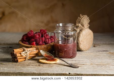 Rasberry jam with cinnamon on rustic background, copy space