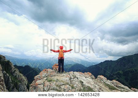 successful young woman backpacker open arms on mountain peak