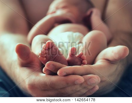 strong male hands holding sleeping newborn baby photo with soft blur effect