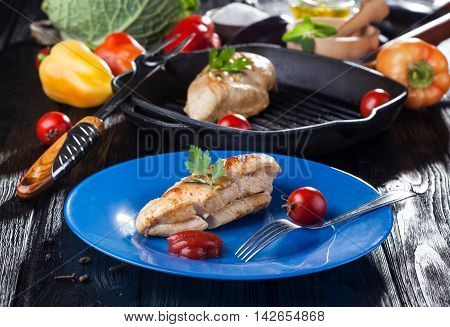 Tasty Grilled chicken fillet and bell pepper on a plate on the black wooden table.