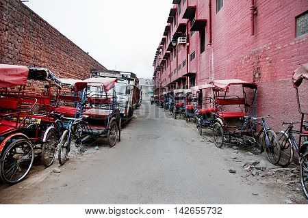 Red rickshaws taxi park in row waiting for passengers background red building