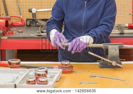 hands with a caliper, the person measures the thread of the pipe with the caliper