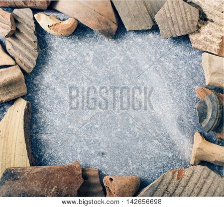 Frame of ceramic shards of antique crockery on marble stone background. Archaeological concept