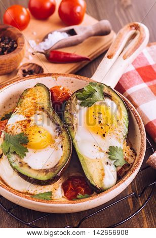Avocado baked with egg on ceramic serving pan.Toned