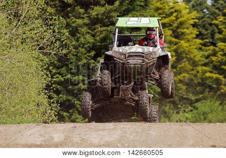 ARNCOTT, UK - MAY 4: Unnamed drivers competing in the UK SXS RZR series land on the top of the table-top jump before heading into a left handed bend on May 4, 2014 in Arncott
