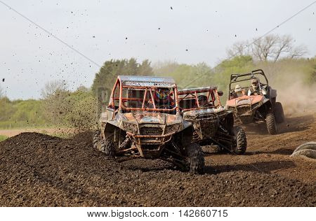 ARNCOTT, UK - MAY 4: Unnamed drivers competing in the UK SXS RZR series round a tight berm and corner at speed before heading toward the finish line on May 4, 2014 in Arncott
