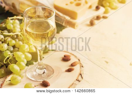 glass of white wine cheese and grapes tinted and copy space.