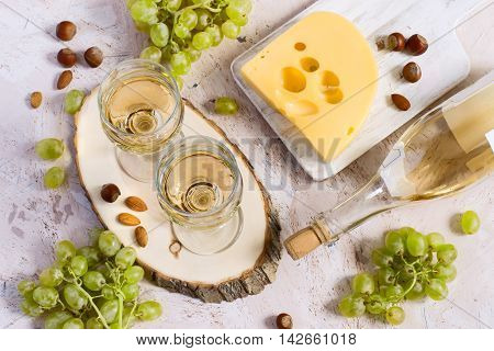Two glasses of white wine cheese and grapes. Top view.