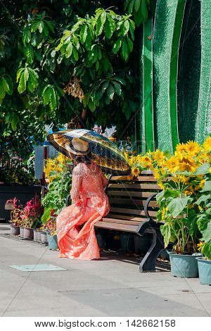 HO CHI MINH CITY VIETNAM - FEBRUARY 07: Woman with umbrella in Ao Dai dress poses for picture during flower festival in Ho Chi Minh City on February 07 2016.