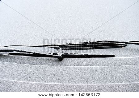 Car wipers covered with snow on a cold winter day