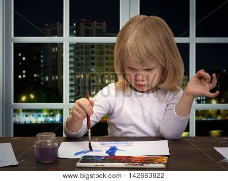 The child draws the table. Girl little blonde. Multicolored paint brush with blue. The window in the building. Outside night city