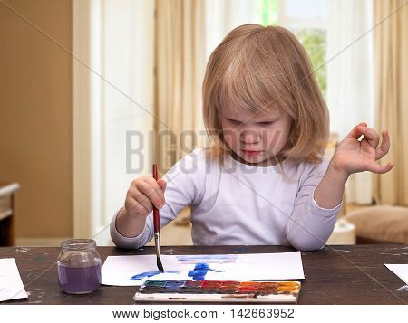 Child at home in a room at the table draws. Girl little blonde. Multicolored paint brush with blue.