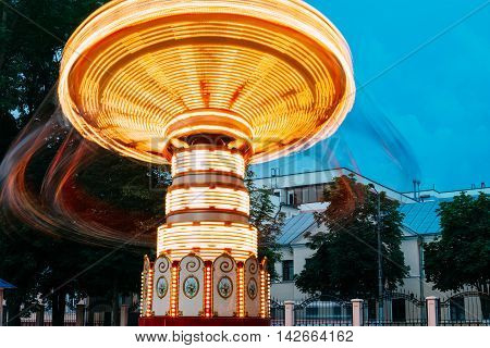 Blurred Motion Effect Around Of Brightly Illuminated Rotating High Speed Carousel Merry-Go-Round. Summer Evening In City Amusement Park.
